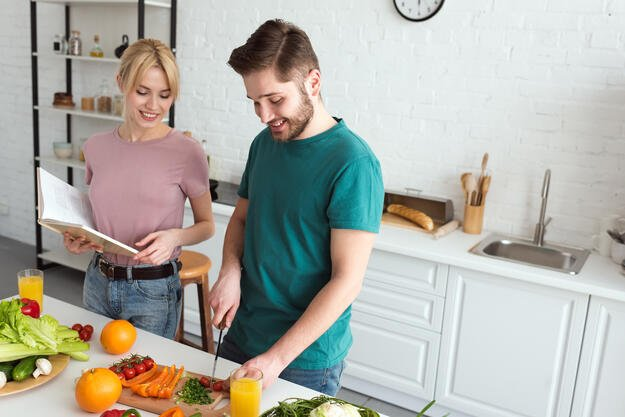 Couple cooking food together smiling
