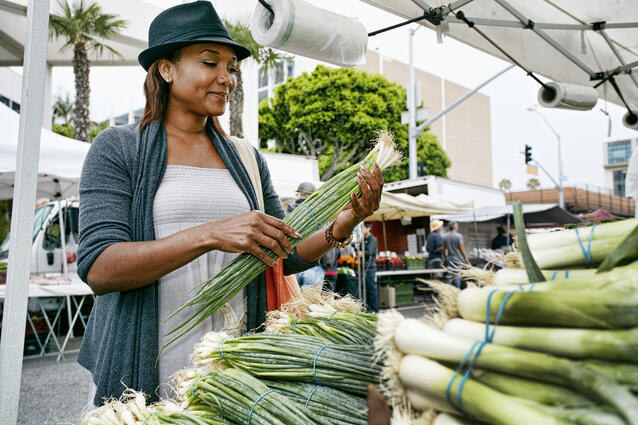 Woman shopping at farmers market for healthy greens