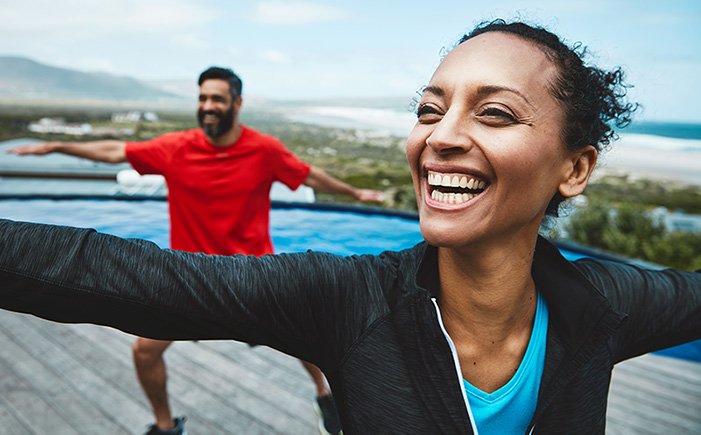 Couple smiling doing yoga and living a healthy lifestyle.