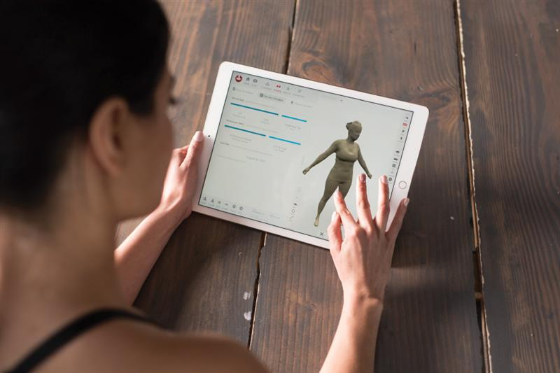 Profile member holding 3D body scan report of her weight loss.