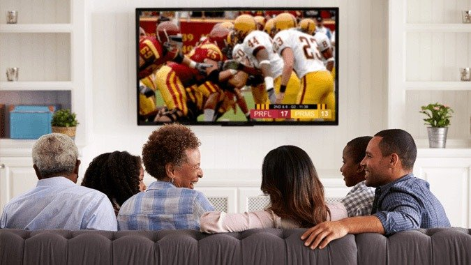 Friends watching sports on a couch while they enjoy healthy foods.
