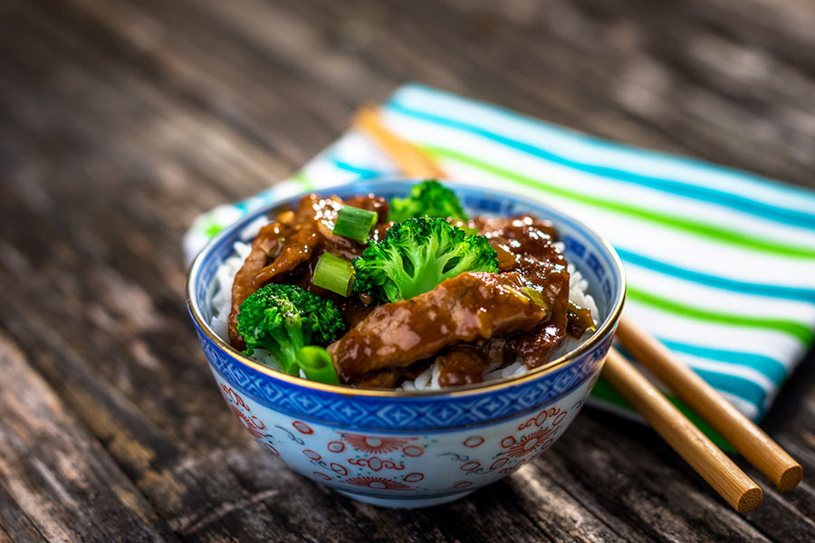 Healthy crockpot beef and broccoli recipe in a bowl with chopsticks.