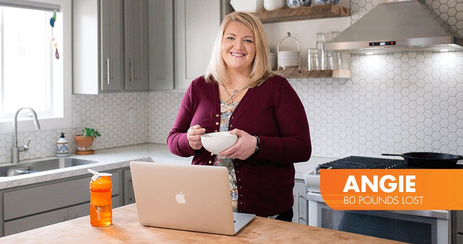 Angie Lost 80 pounds with Profile by Sanford. Photo of Angie with a bowl standing with her laptop in her kitchen.