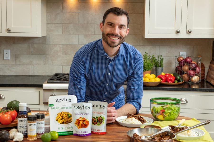 Man in a kitchen with Kevin's Natural Foods products