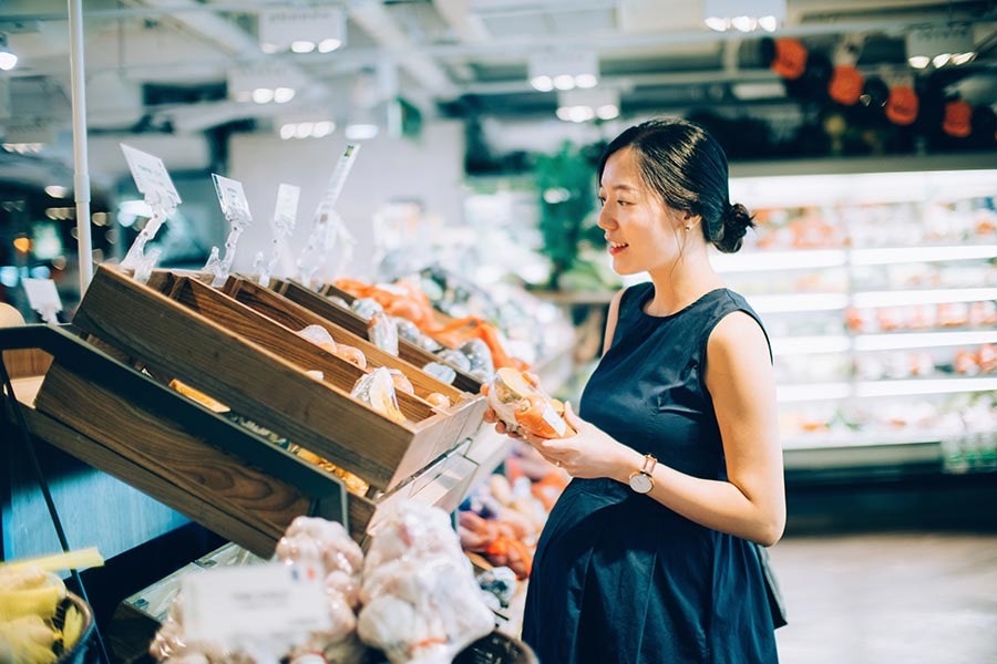 pregnant woman picking out vegetables